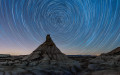 Long exposure taken in the natural area of Bardenas Reales of Navarre, Spain. This is a semnidesertic clay region eroded by rain and winds. The  natural monument in the image center is named Castildetierra. All stars seem to rotate around the Polar star which is always located at North in the Northern hemisphere.